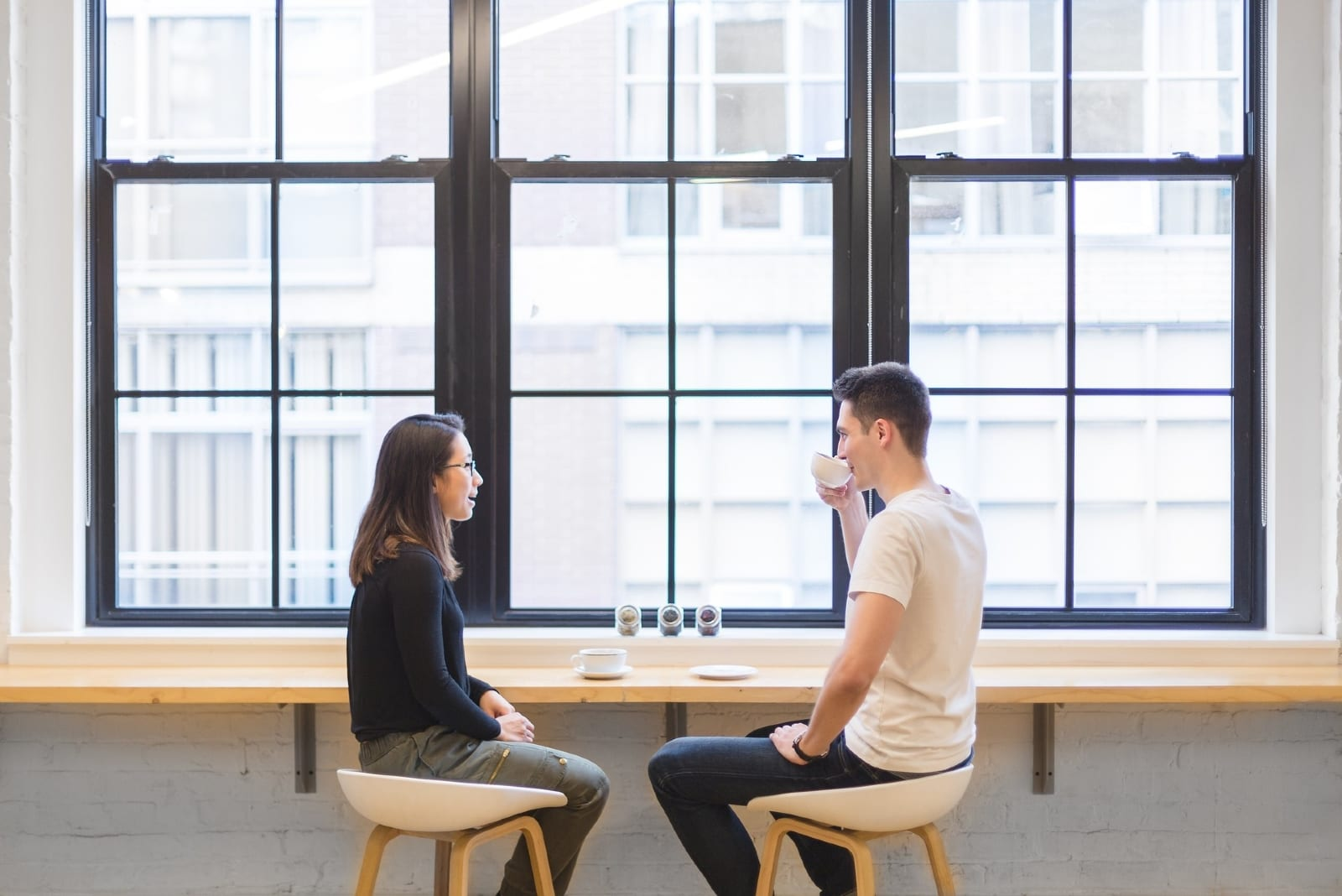 man and woman talking while sitting at table