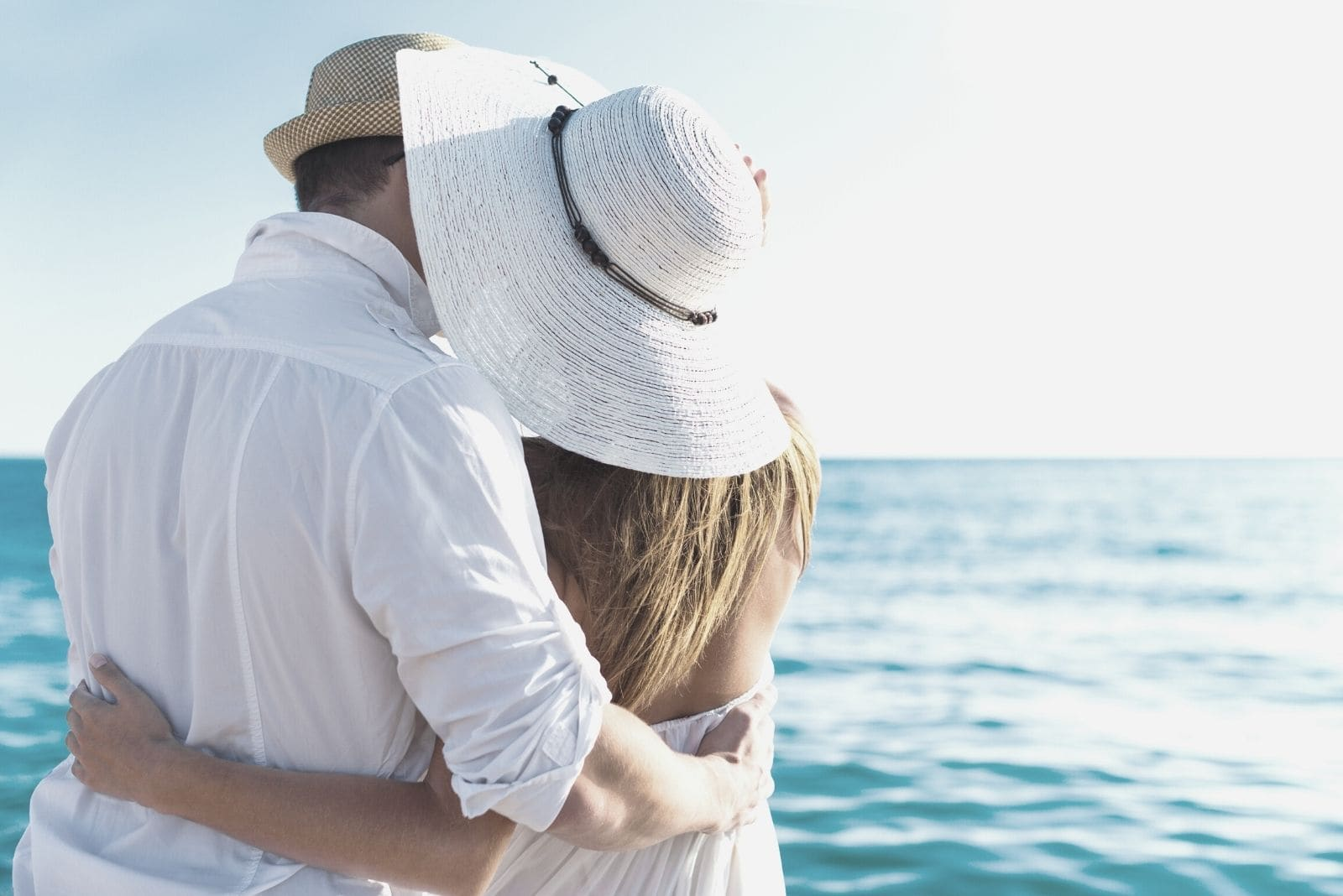 happy couple hugging facing the sea in a vacation to a tropical place