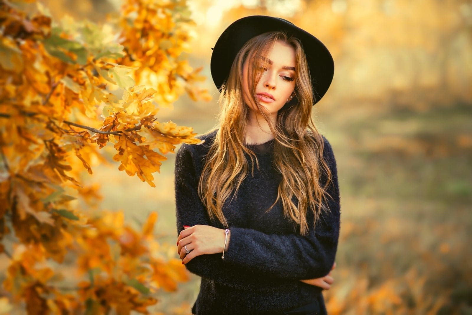 woman wearing black dress and hat standing with arms crossed in the autumn park thinking deeply