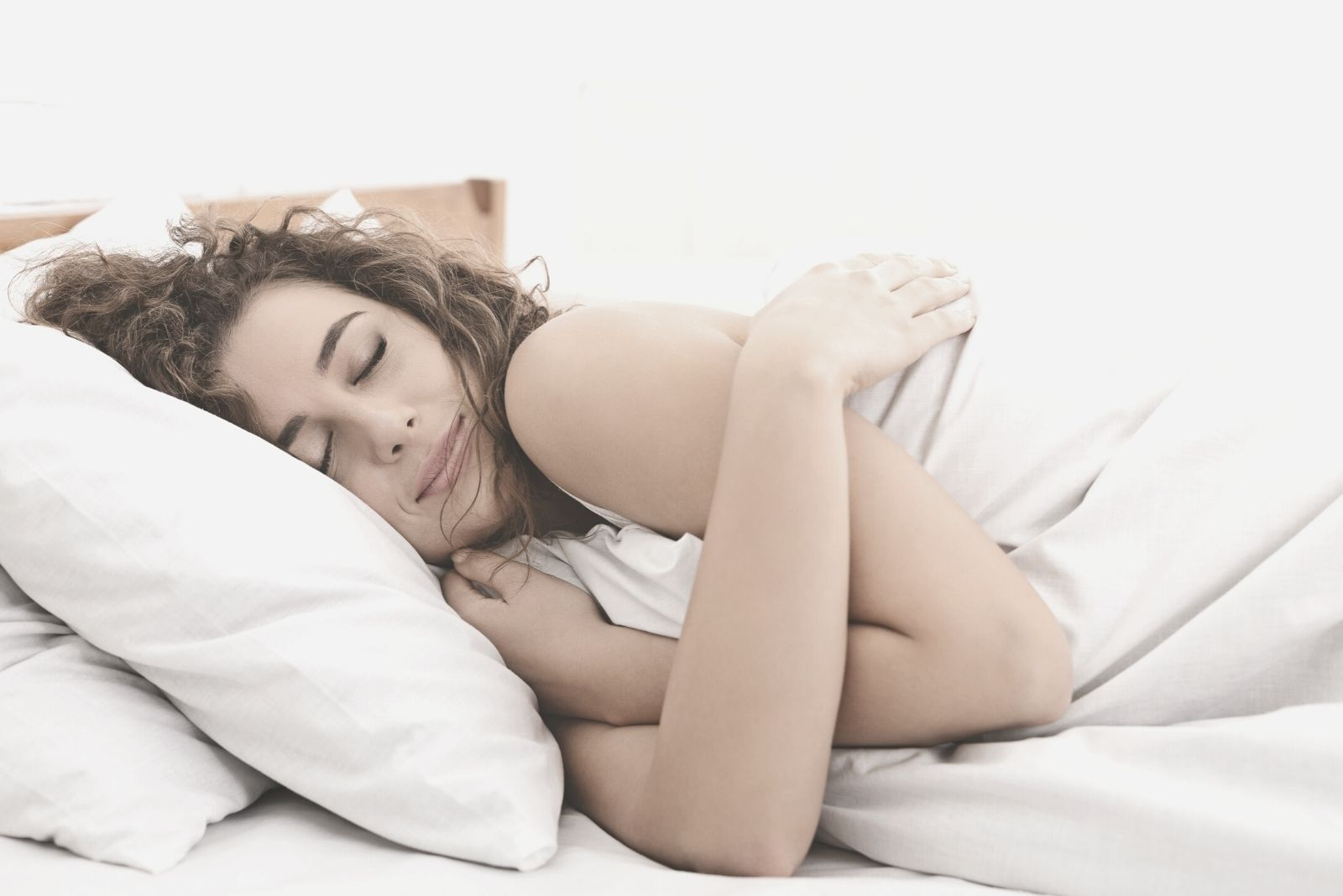 pretty young woman hugging herself to dream while lying down in bed