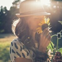 in nature stands a woman with a flower she smells