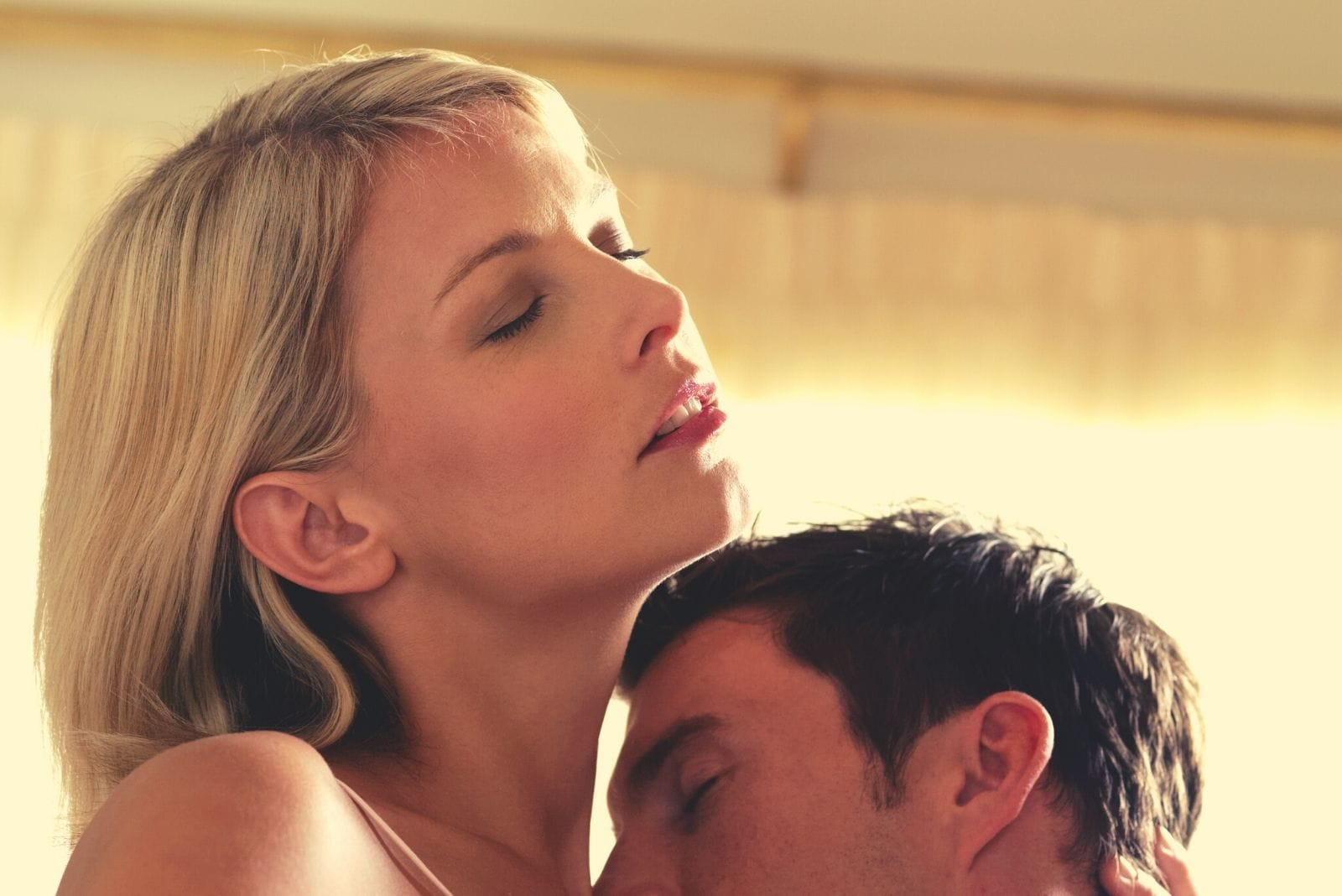 a young couple kiss passionately inside the room