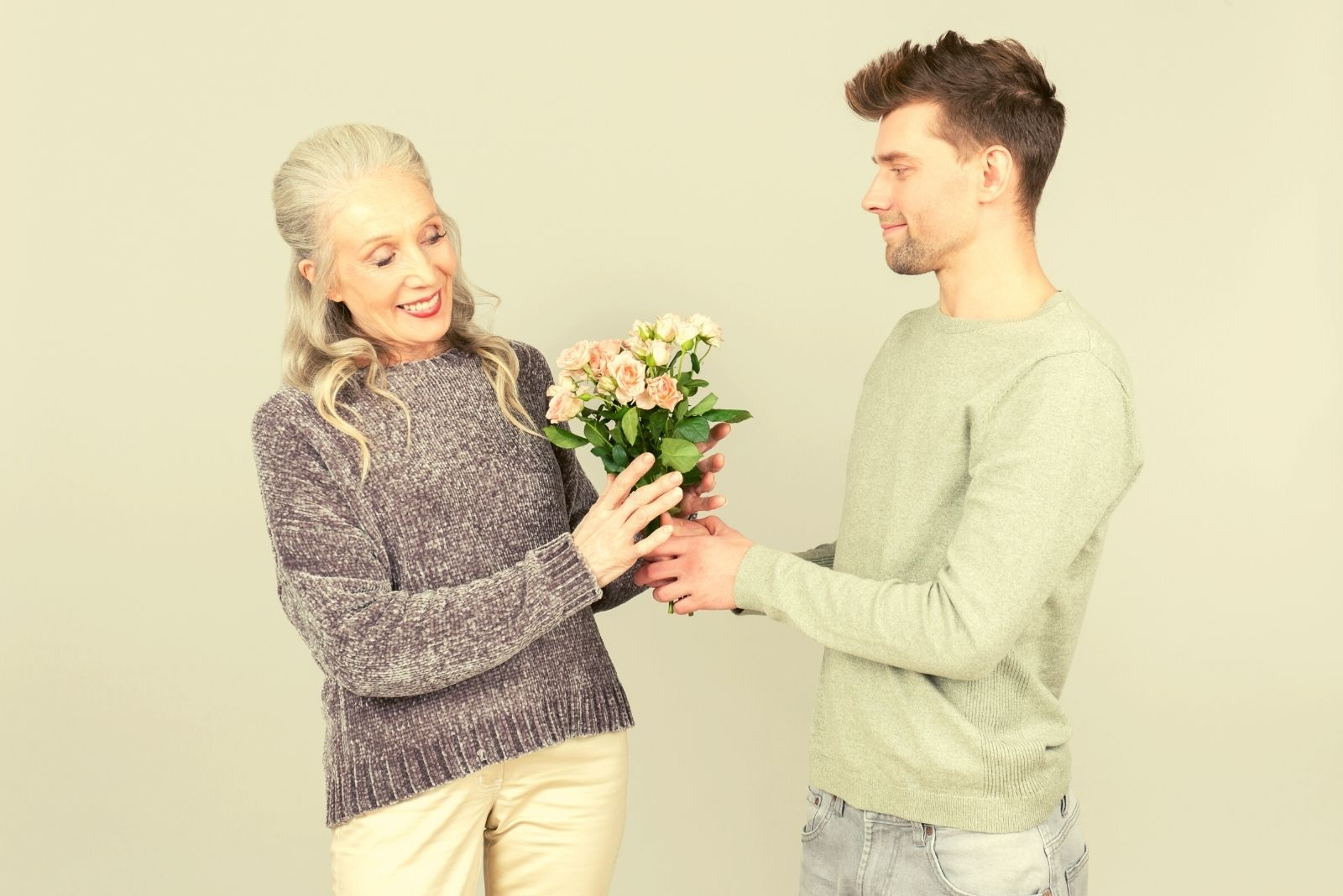 age gap love of a younger man giving flower to a mature woman