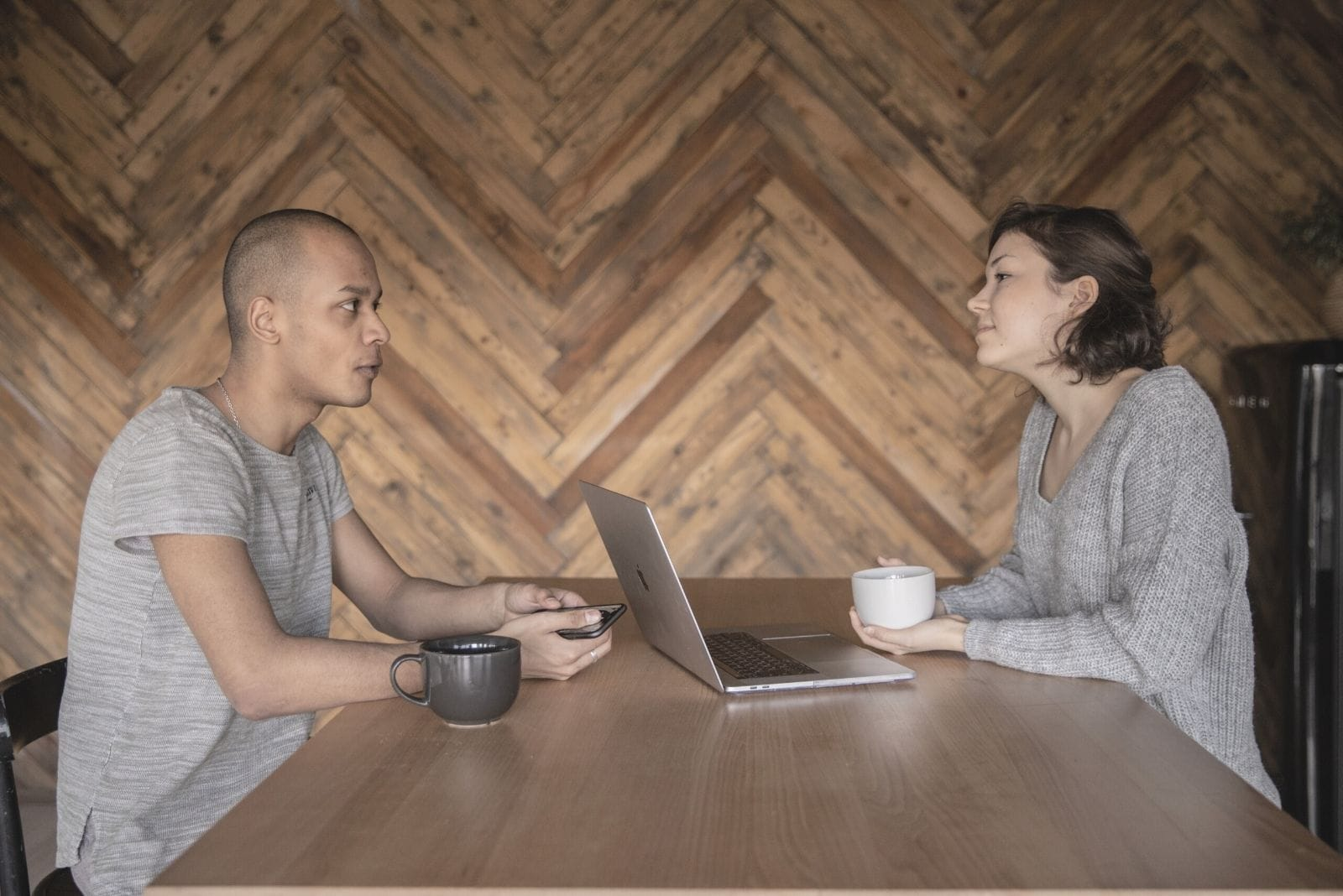 asian couple talking inside a cafe with a laptop and coffe at the table