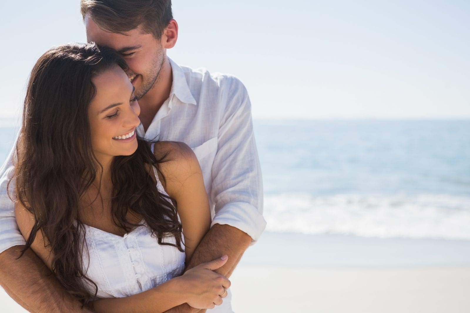 attractive couple cuddling sweetly in the beach wearing white top/dress