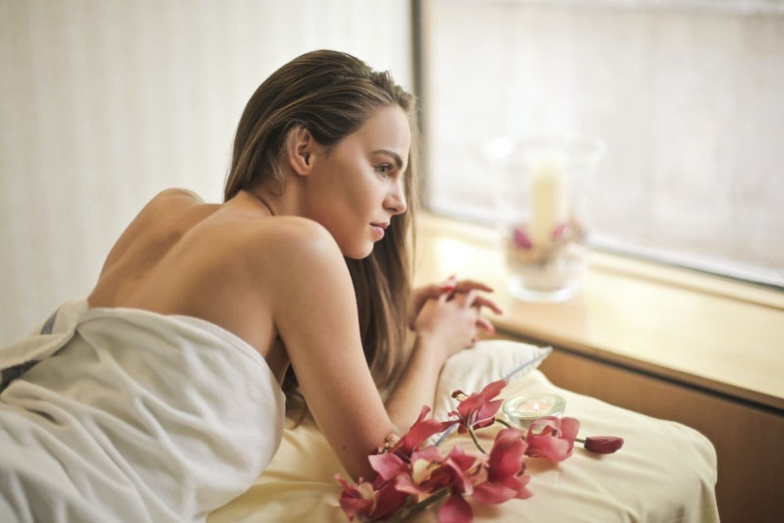 beautiful young woman lying down on the spa bed wearing towel facing the windows with lot of flowers around