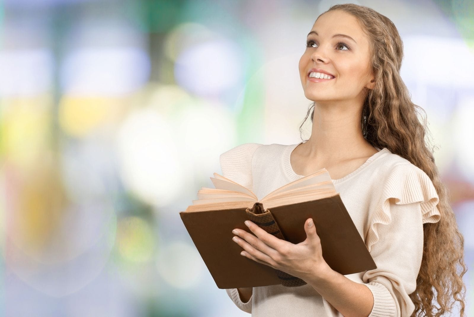 bible and praying woman standing and smiling looking above with a blurred background