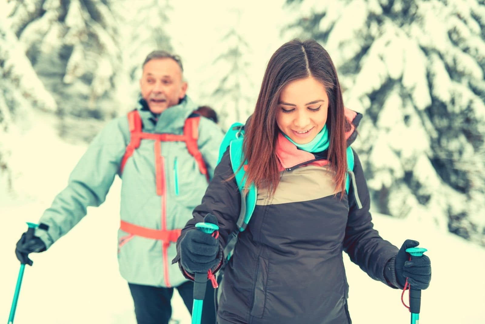 big age gap couple hiking in the snowy mountains with ski