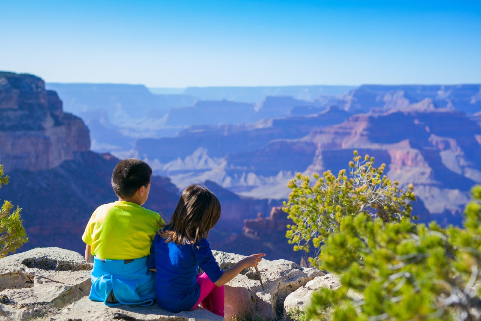 boy and girl sitting on rock looking at mountain