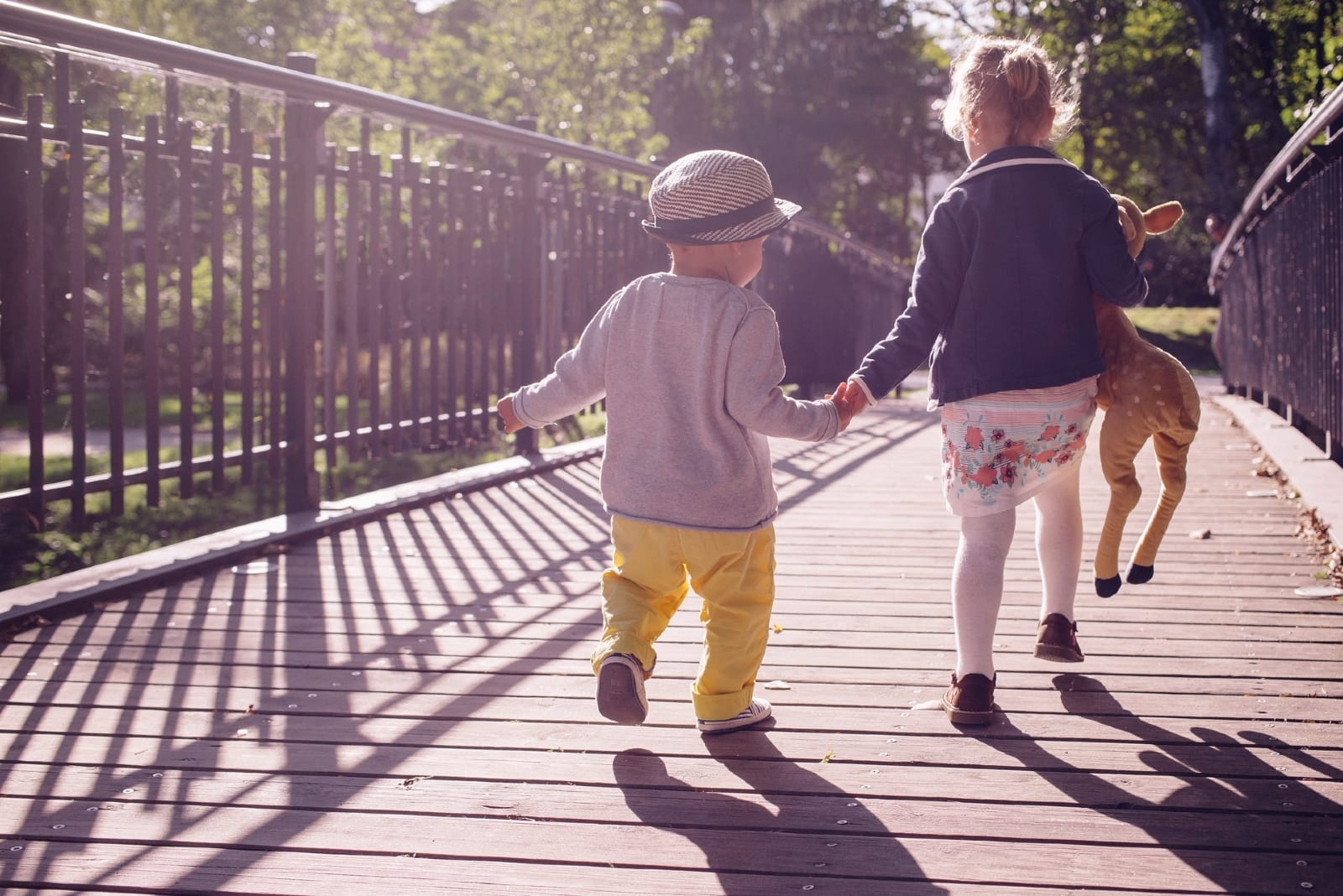 boy and girl holding hands while walking on bridge