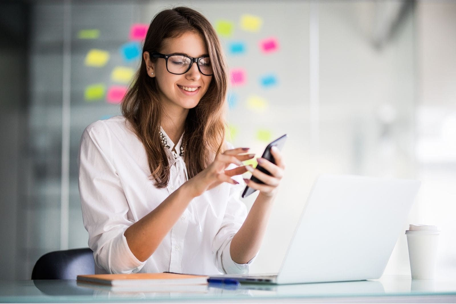 businesswoman in the office browsing her smartphone during the day