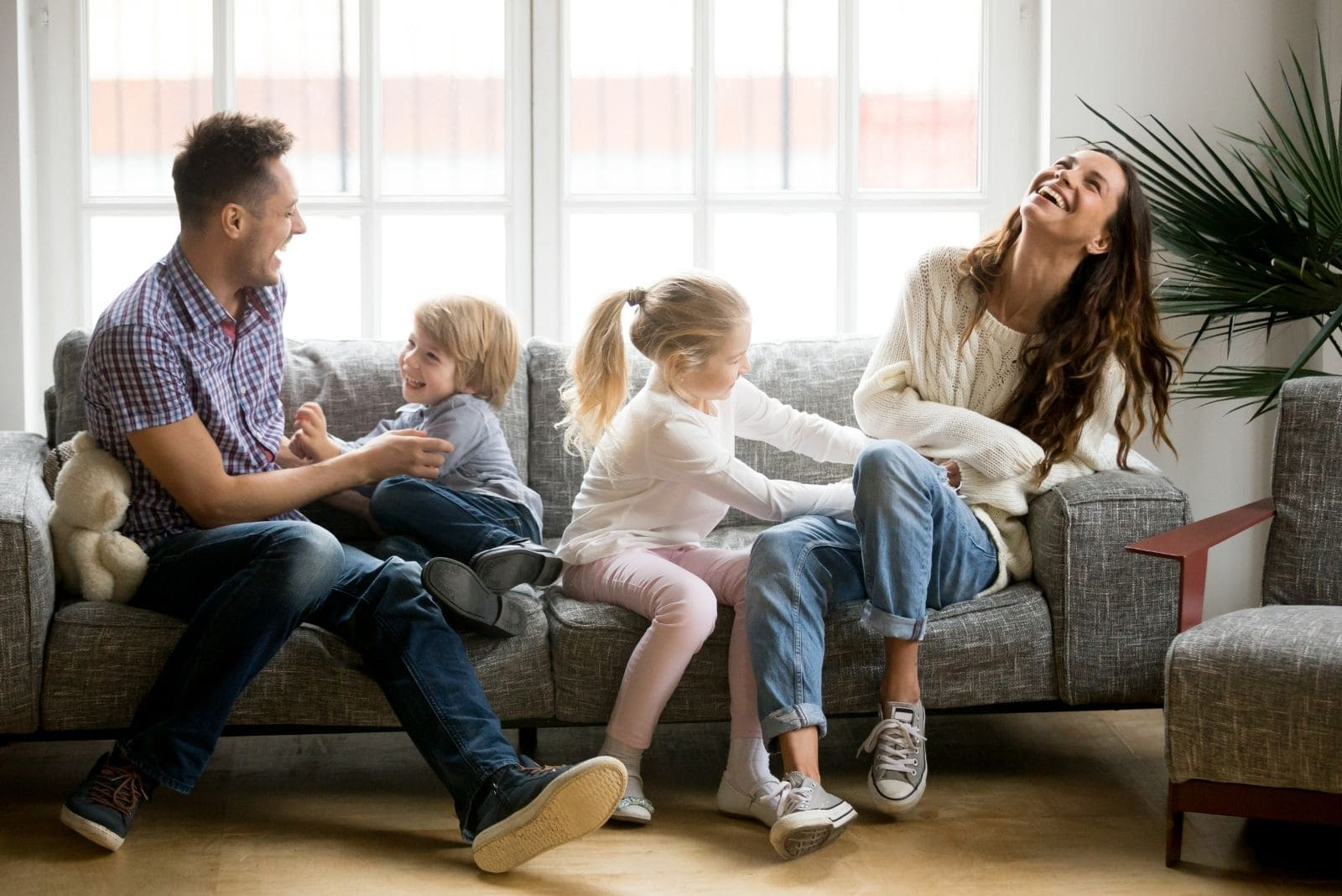 cheerful family playing in the livingroom sitting in the sofa laughing