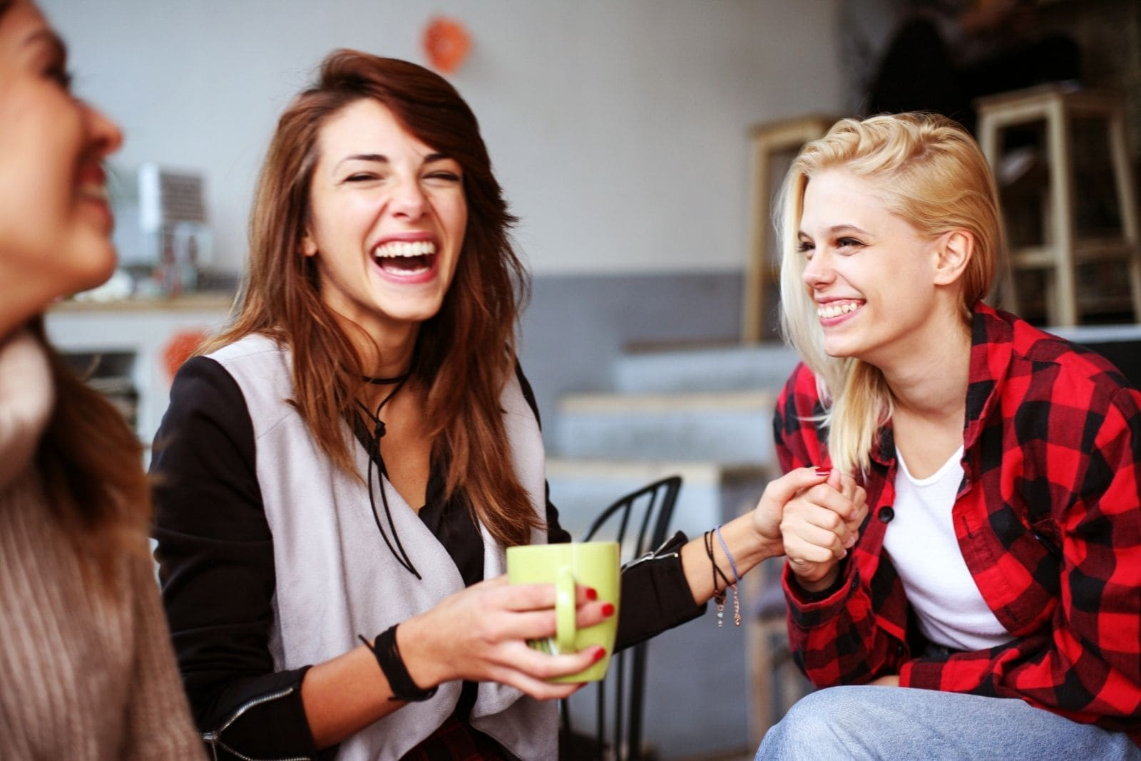 cheerful female friends laughing and drinking coffee at the same time at the cafe/livingroom
