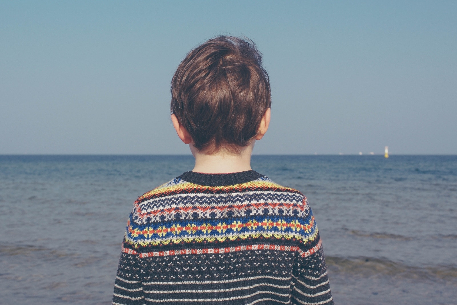 child in multicolored sweater looking at sea