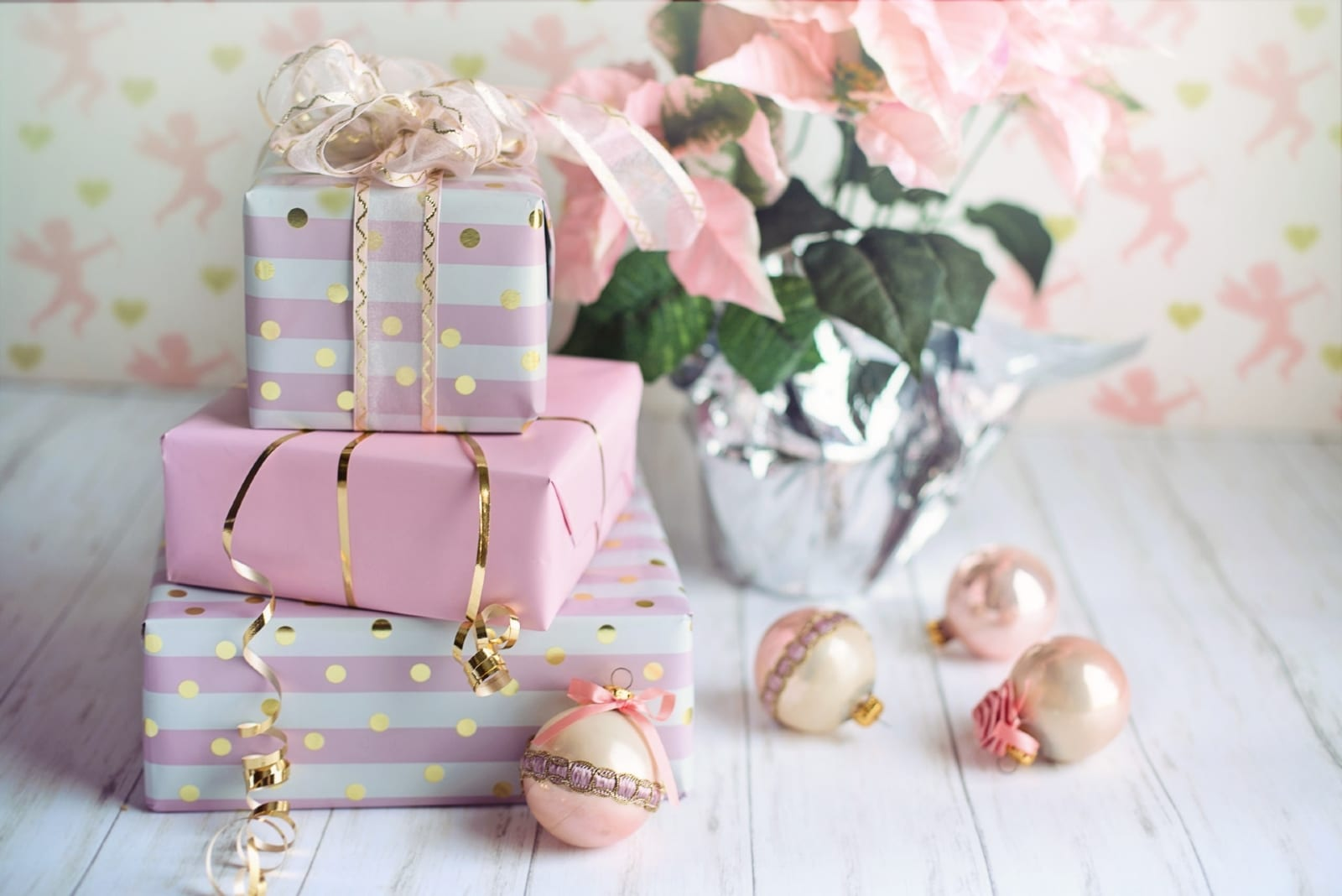 christmas presents on wooden table near pink flowers