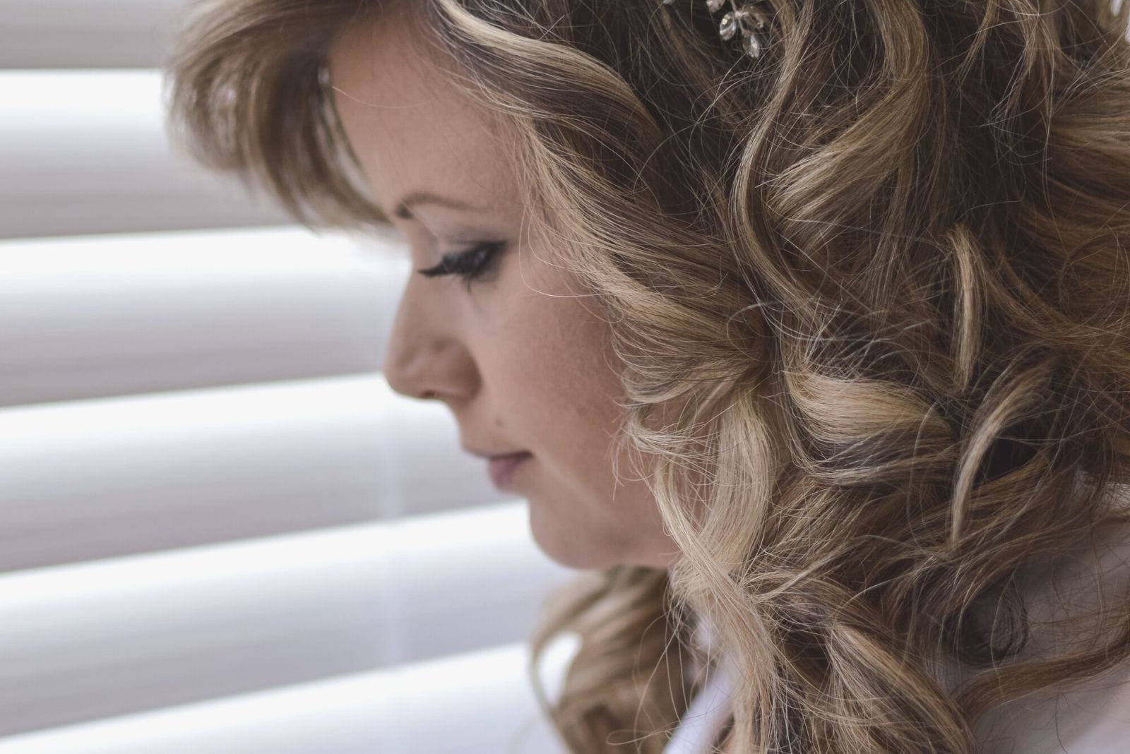 close up sideview photo of a woman standing near the venetian blinds of the room window