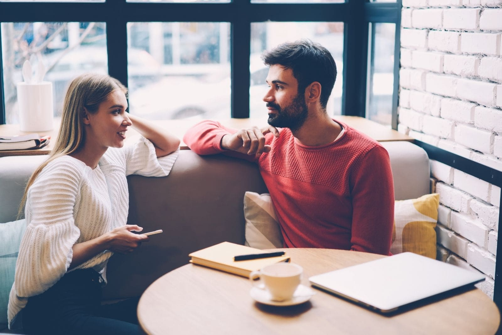 college man and woman talking inside the cafe with coffee on table