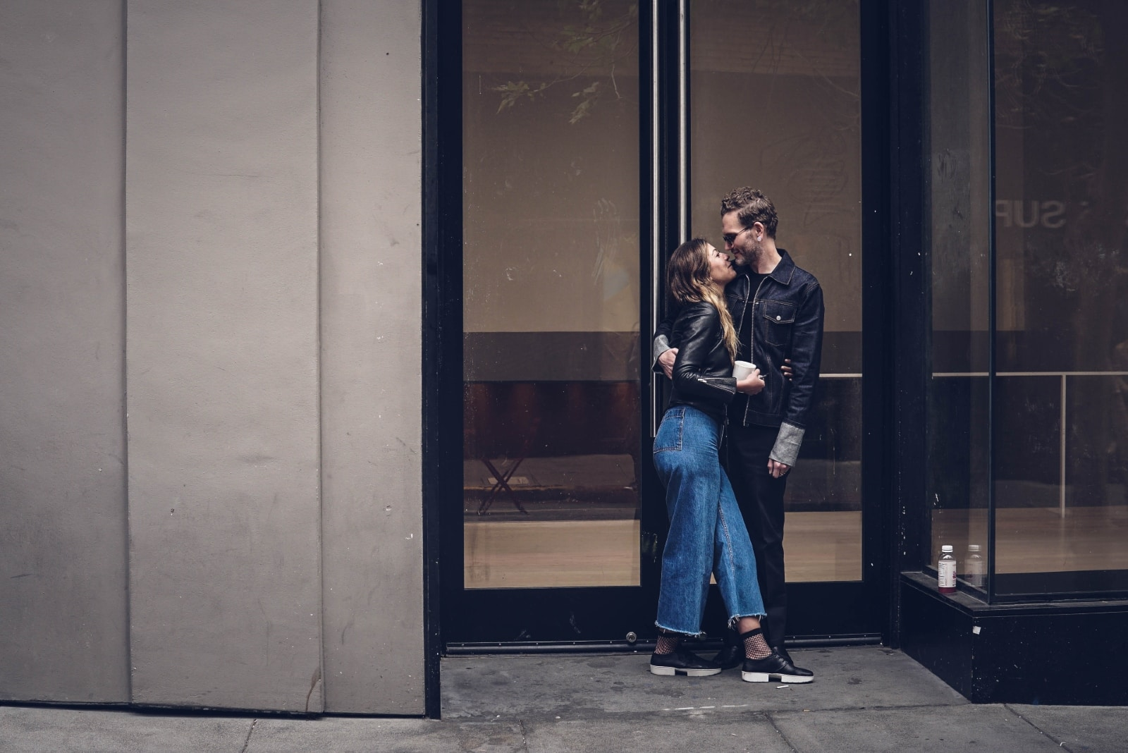 man and woman about to kiss while standing near glass door