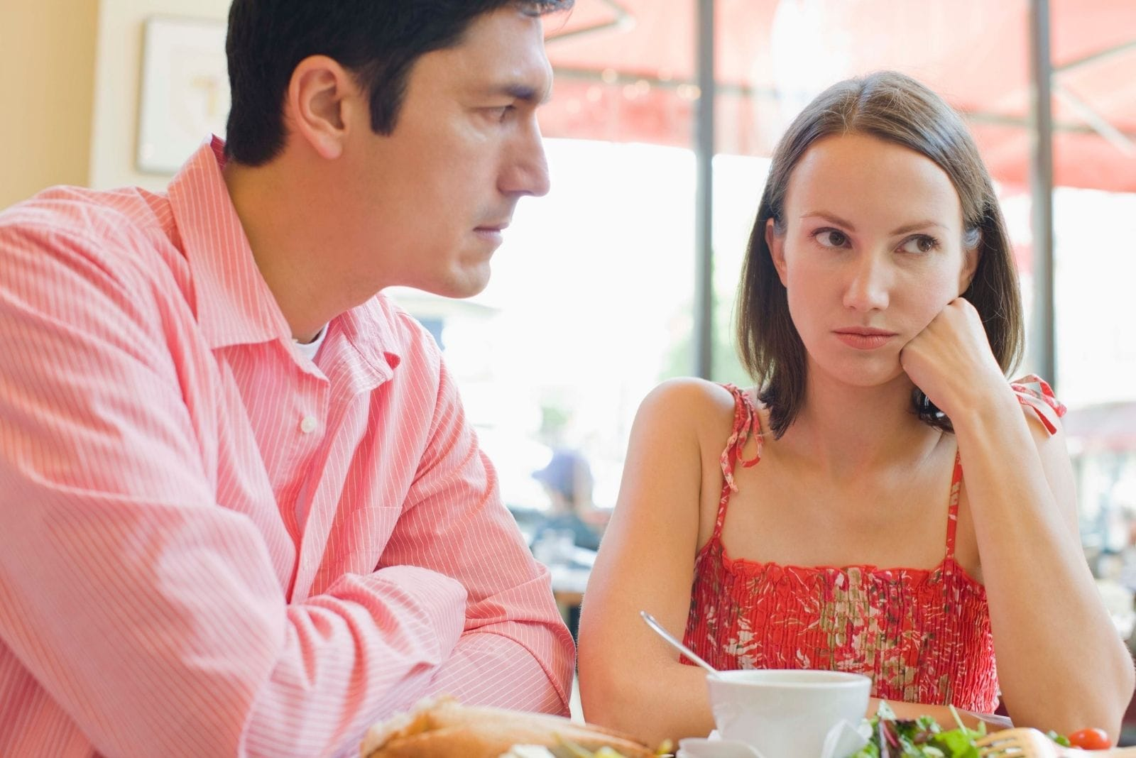 couple arguing in cafe sitting by the table during the day