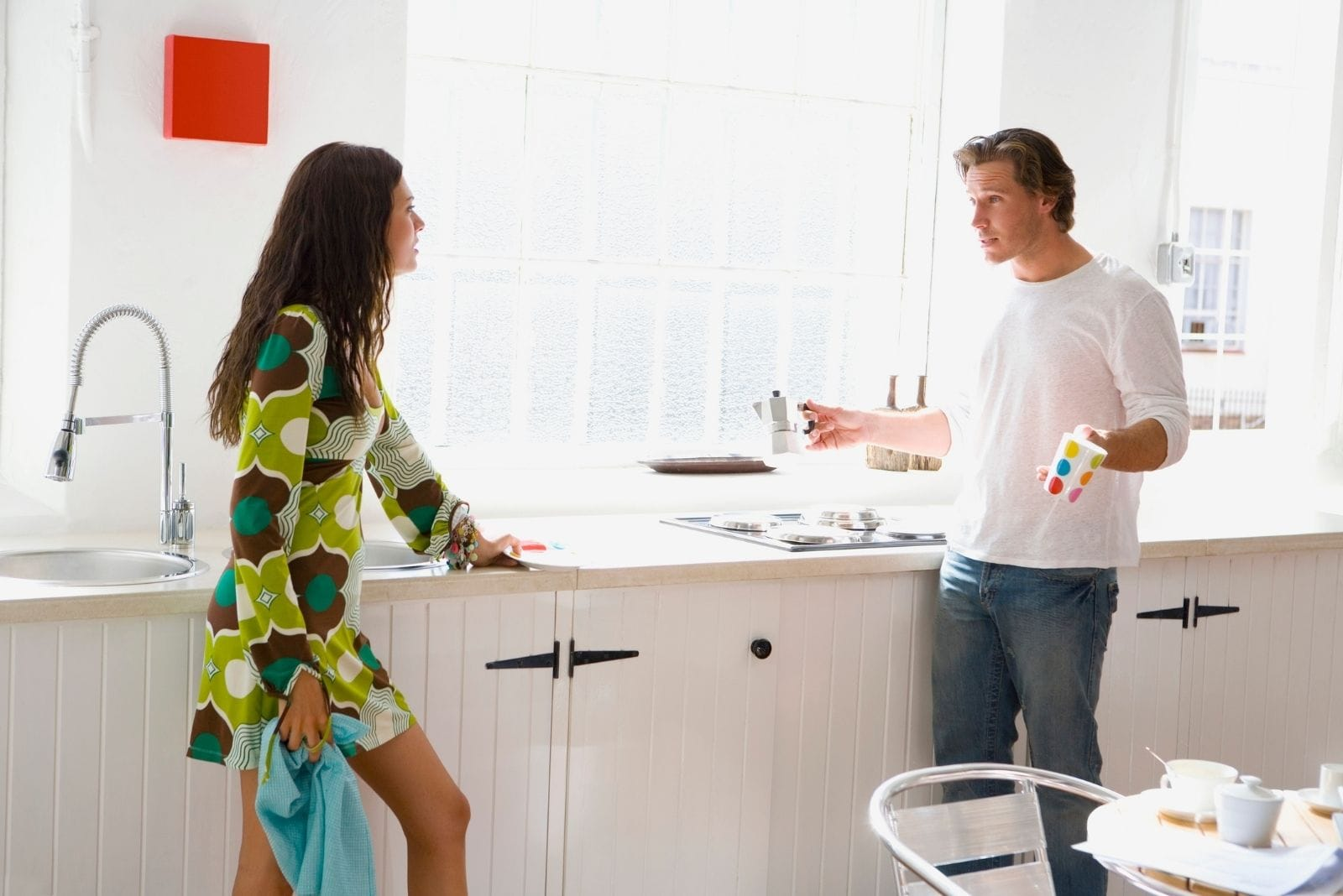 couple arguing in kitchen while cleaning dishes in the kitchen sink
