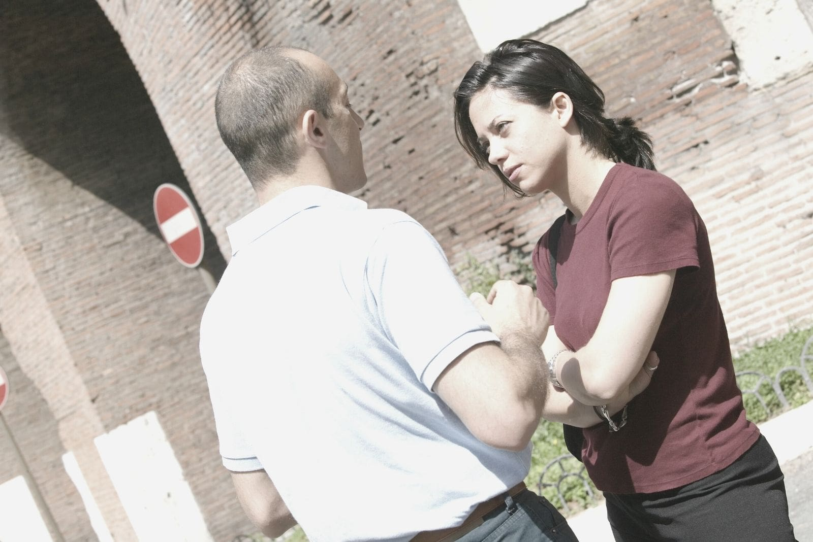 couple arguing outdoors standing near a brick wall building