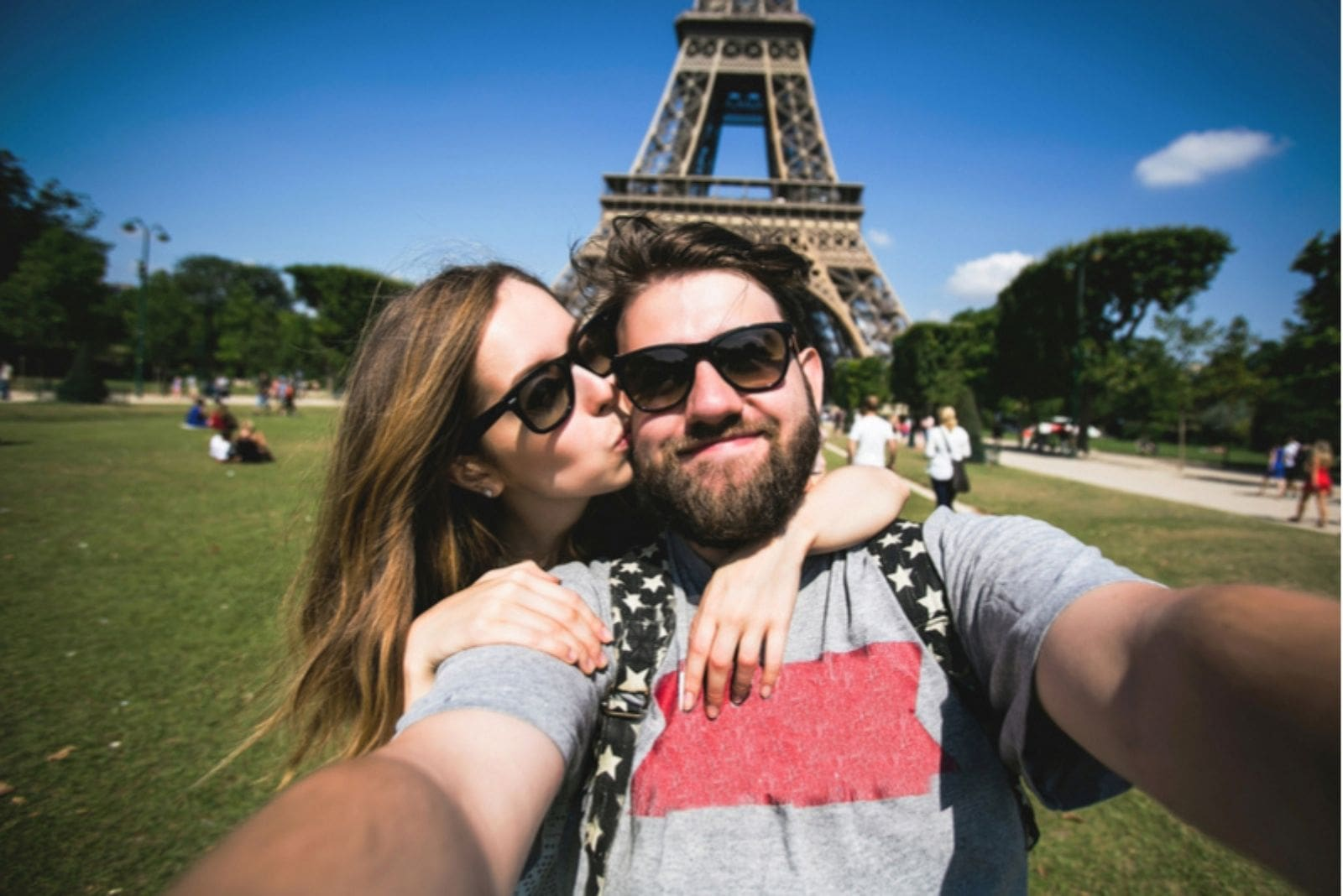 couple at the eiffel tower France posing with the woman kissing and hugging the man