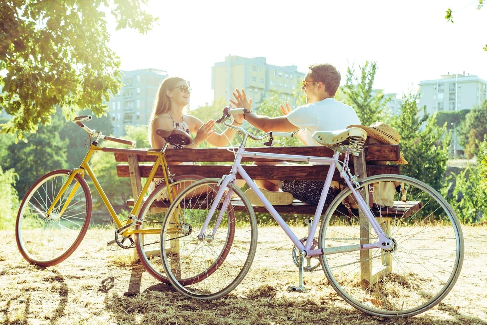 couple boyfriend and friend resting on bench with 2 bicycles beside
