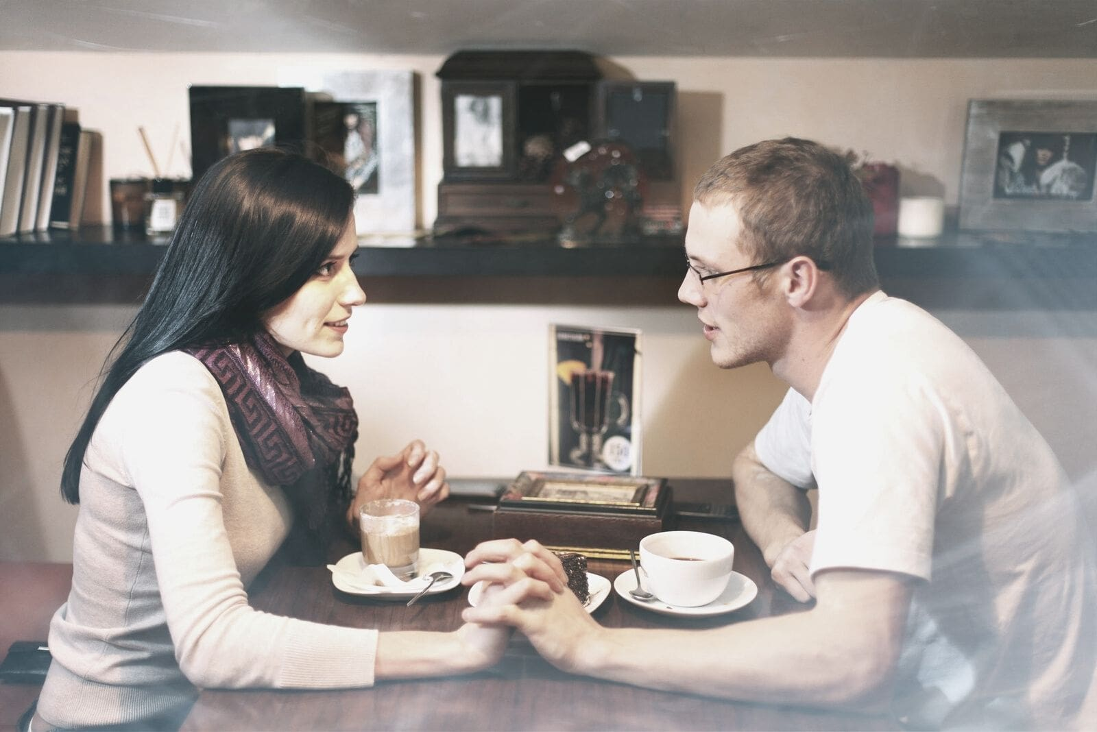 couple cluthching hand while having coffee inside a cafe