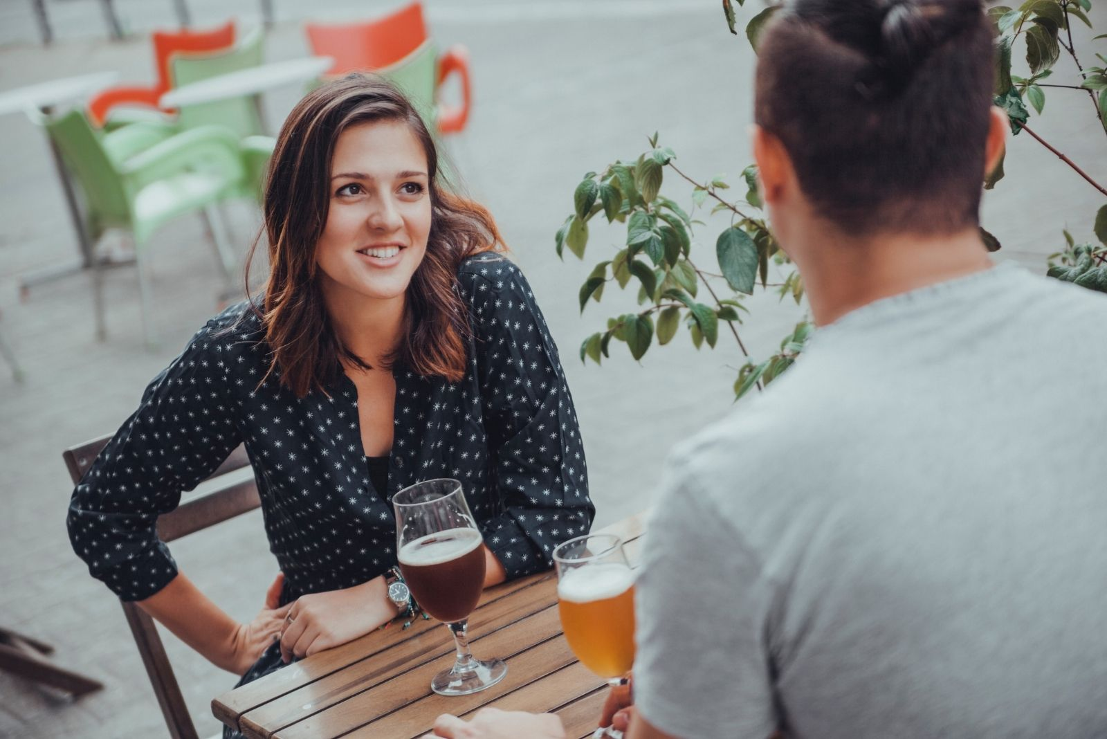 couple drinking outdoors beer and talking seriously
