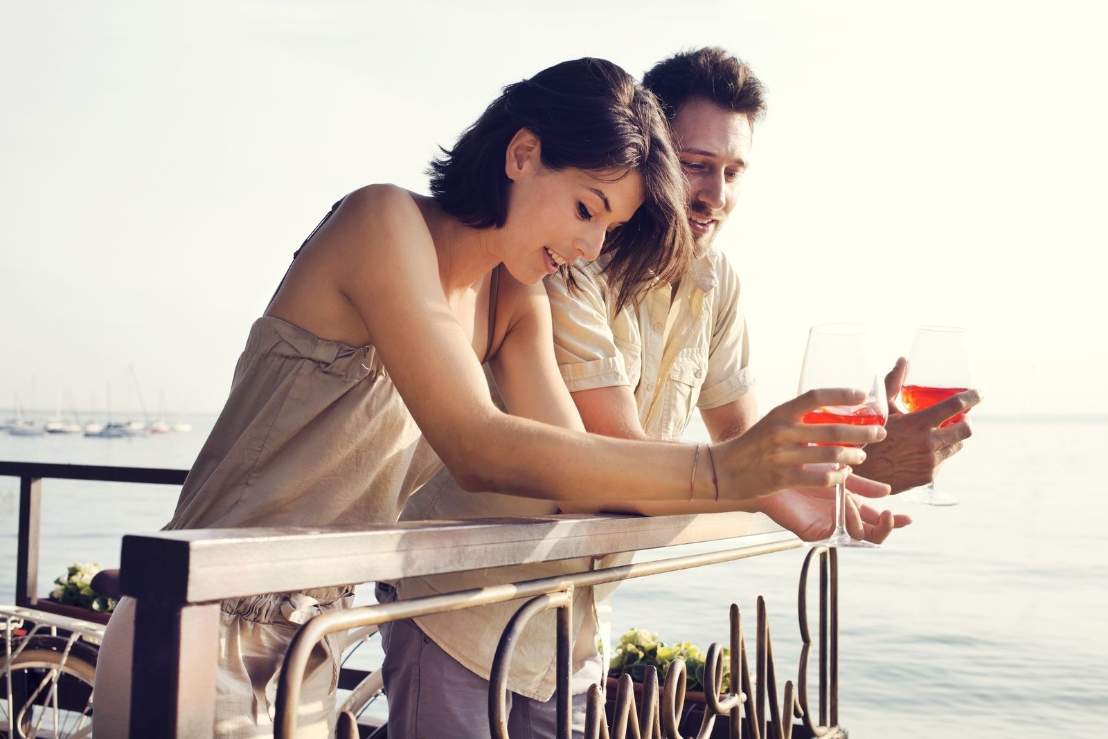 couple drinking wine while standing at an outdoor restaurant near the sea