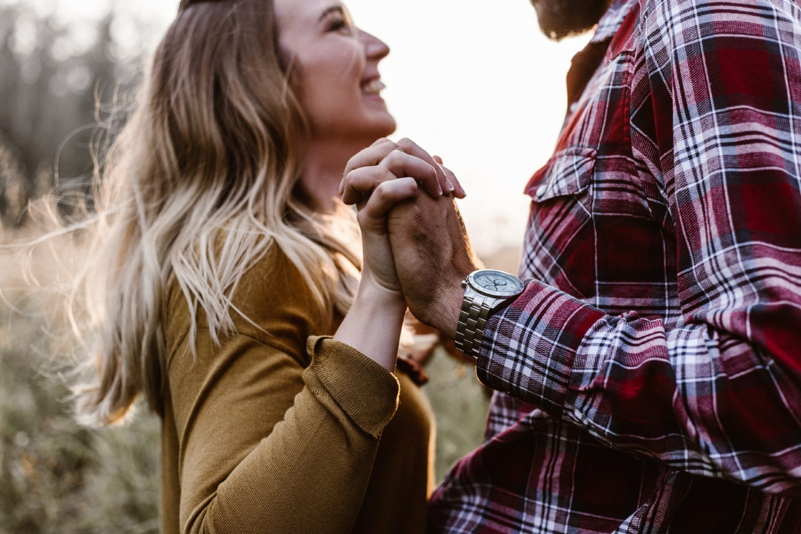 happy woman and man holding hands while standing near trees