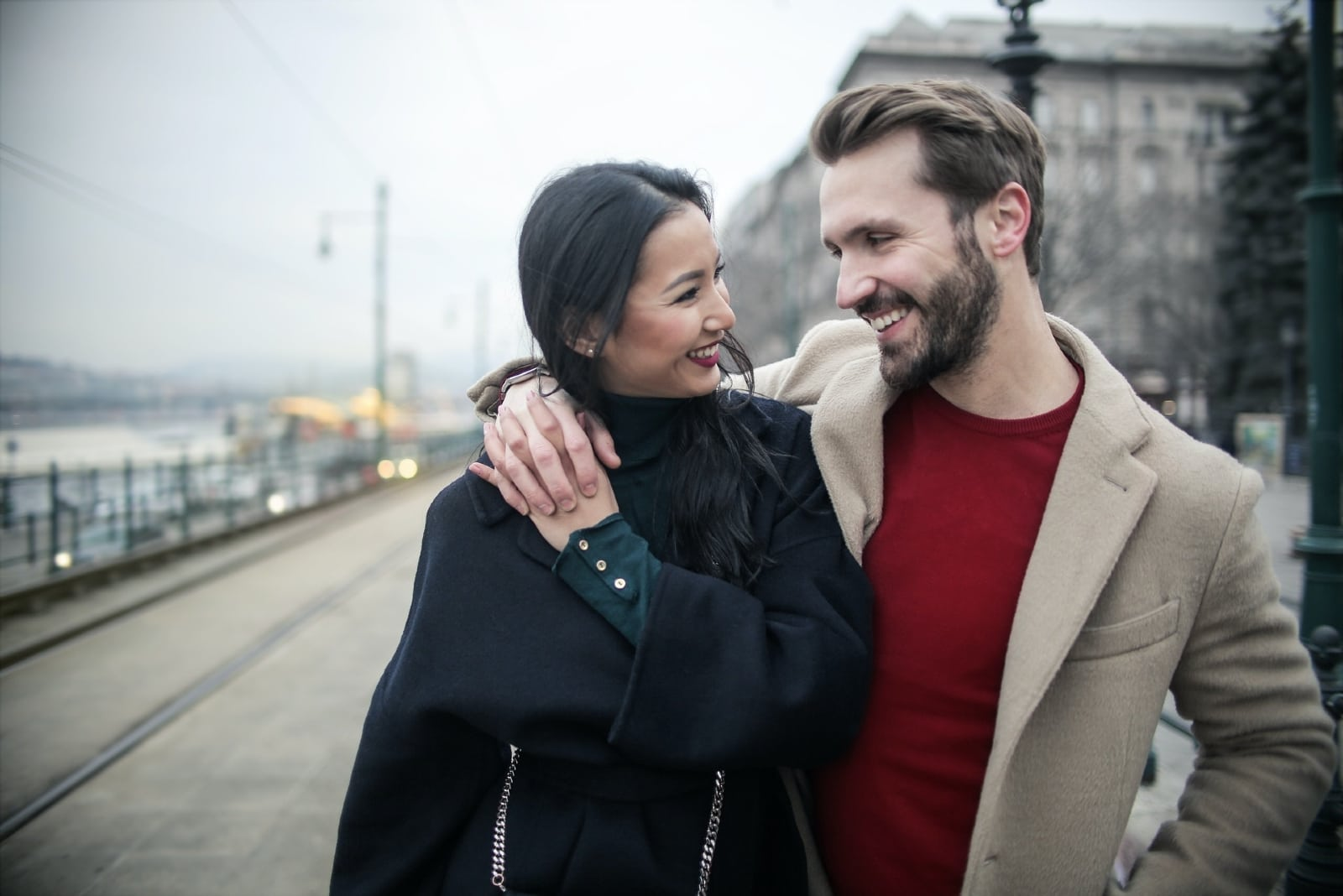 woman in black coat and man holding hands outdoor