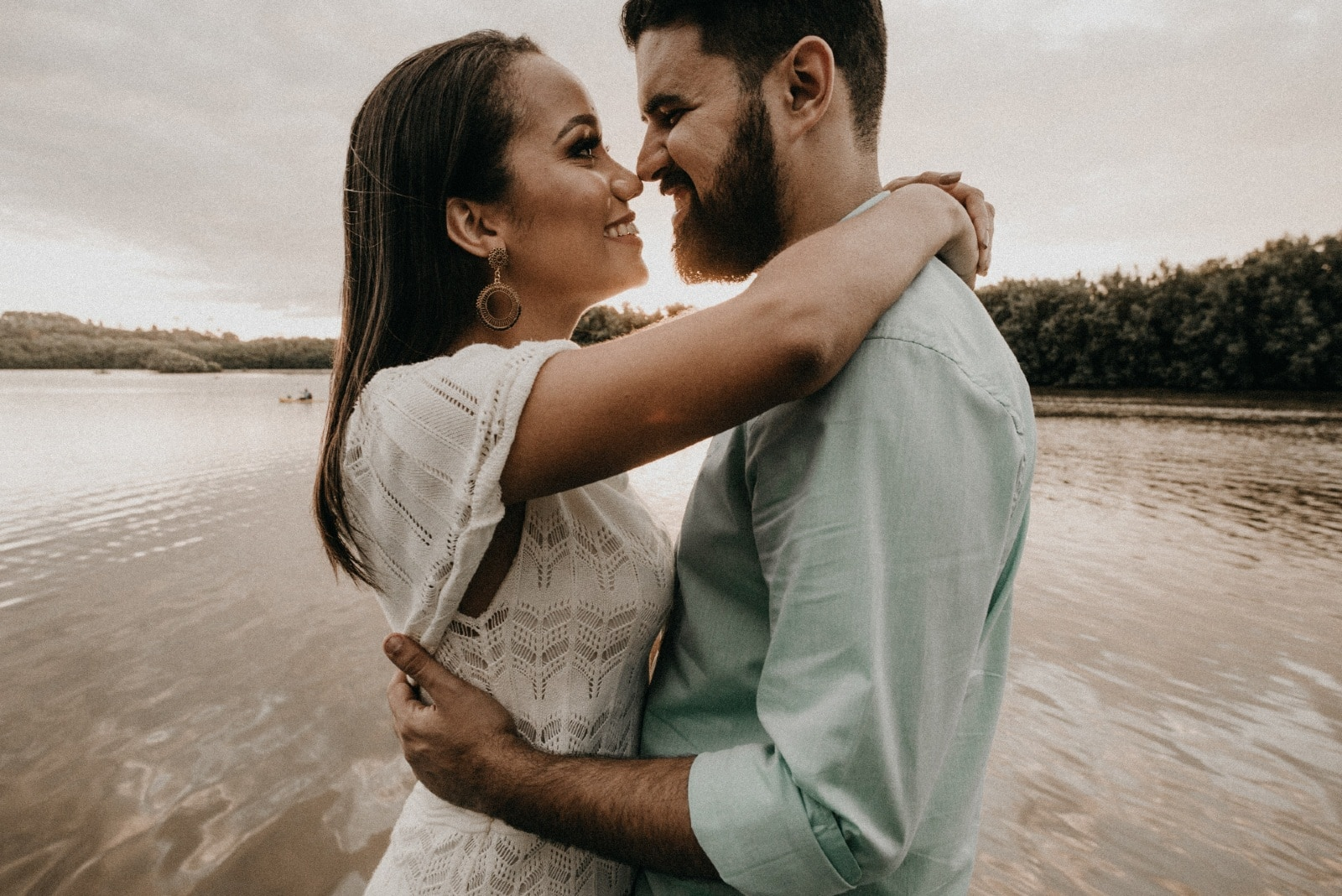 man and woman hugging while standing near water