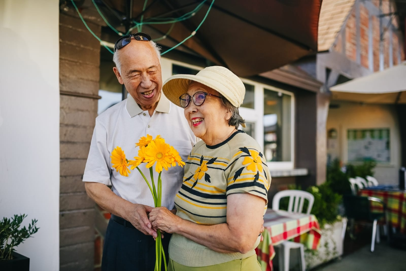 woman with bouquet of flowers and man hugging outdoor