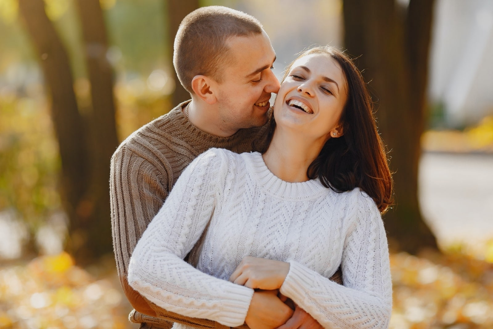 man and woman in sweaters hugging on street