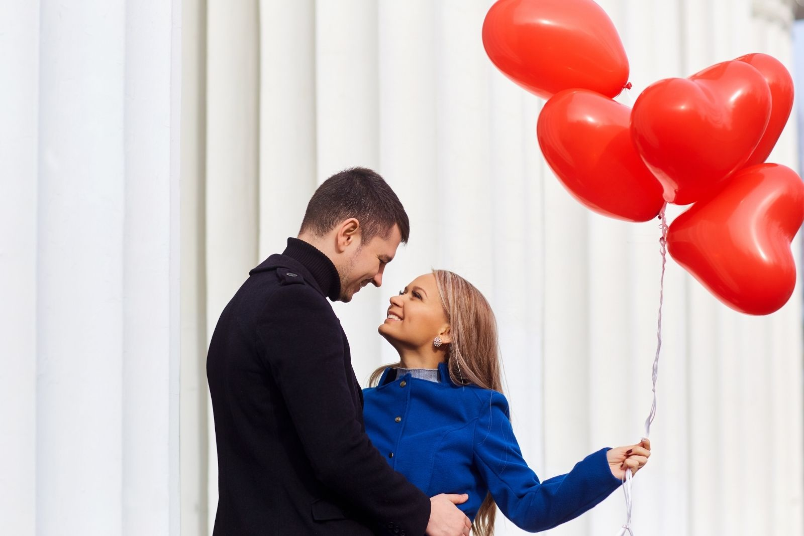 couple hugging with red heart balloons held by the woman