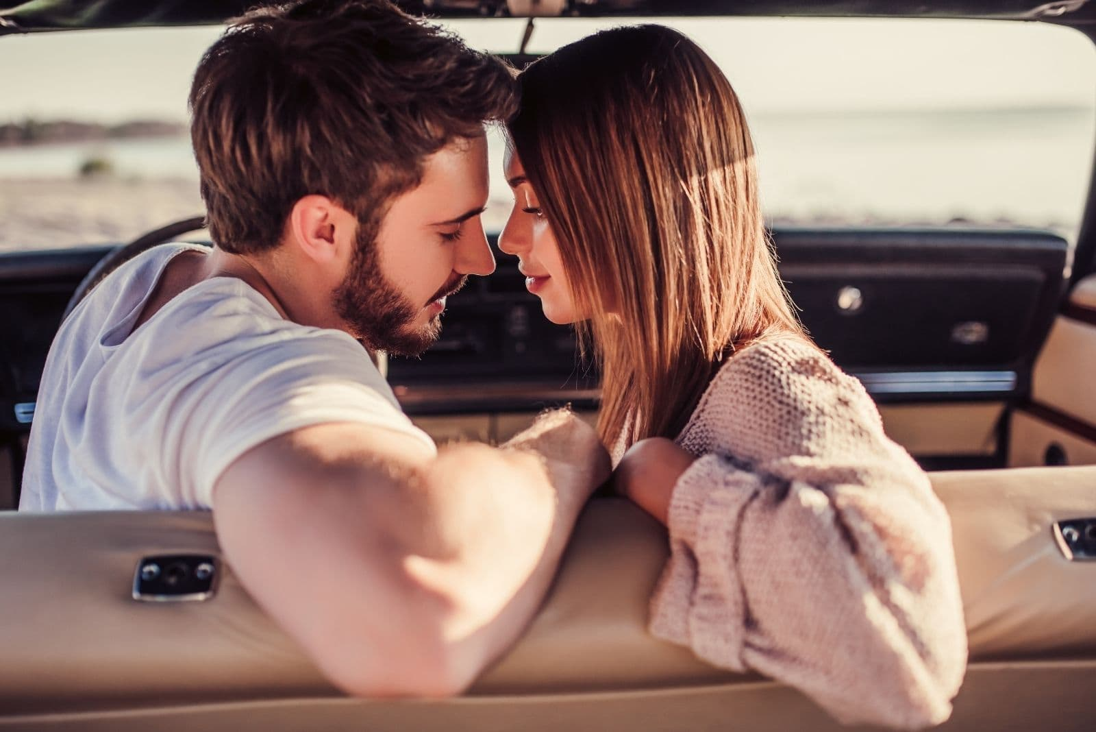 couple in a retro car passionate about to kiss sitting
