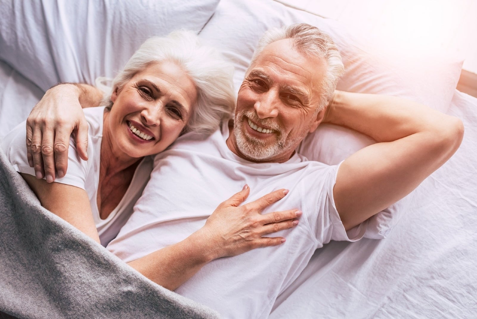 man and woman hugging while laying in bed