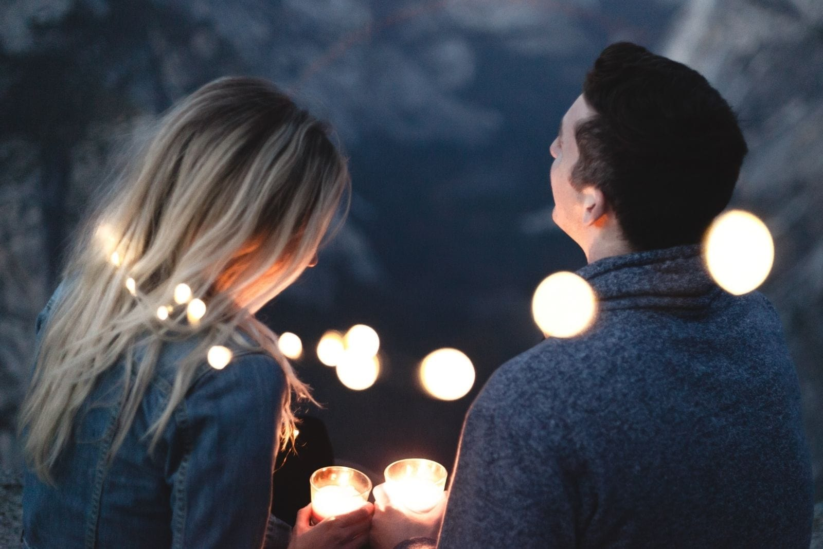 couple in love with lights covering around them holding candles