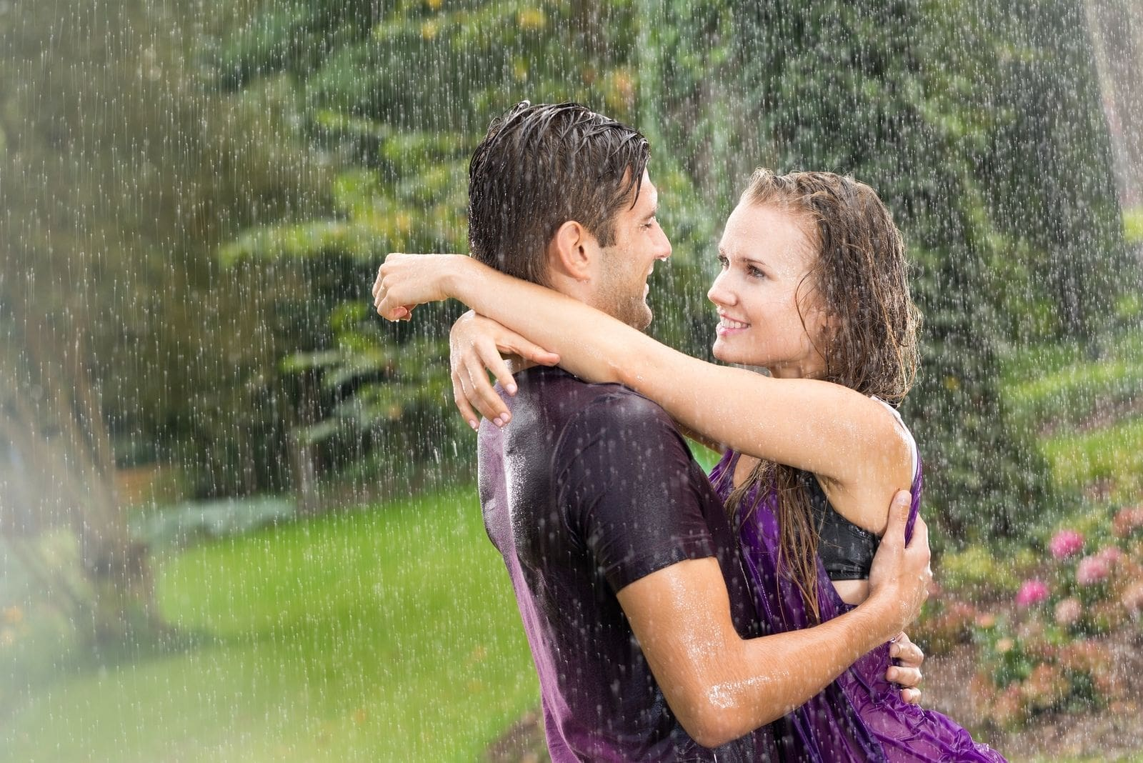 couple in the rain hugging getting drenched with rainwater outdoors