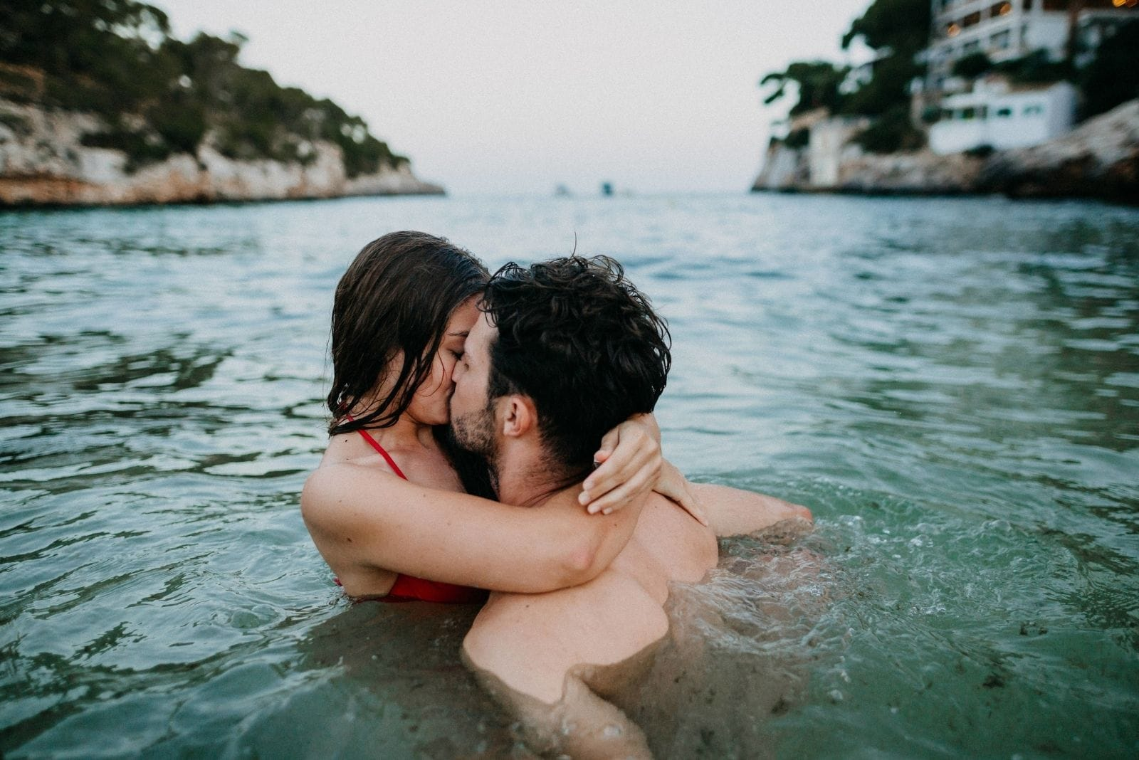 couple in the water kissing passionately wearing swimwear