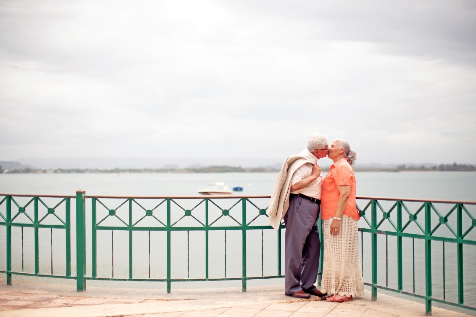 man and woman kissing while standing near water