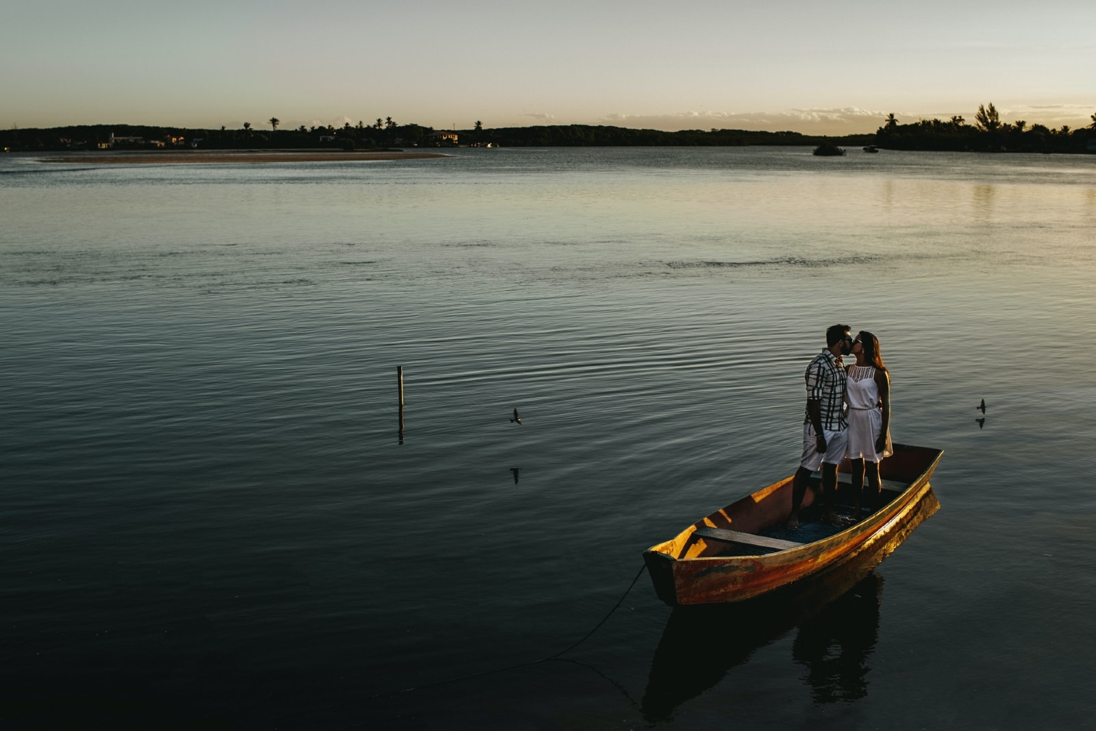 man and woman kissing while standing in boat