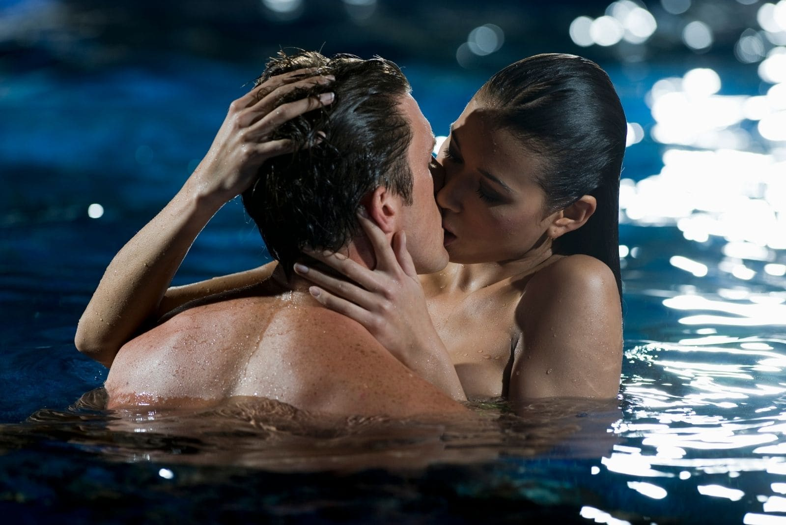 couple kissing in the pool soaking wet and naked