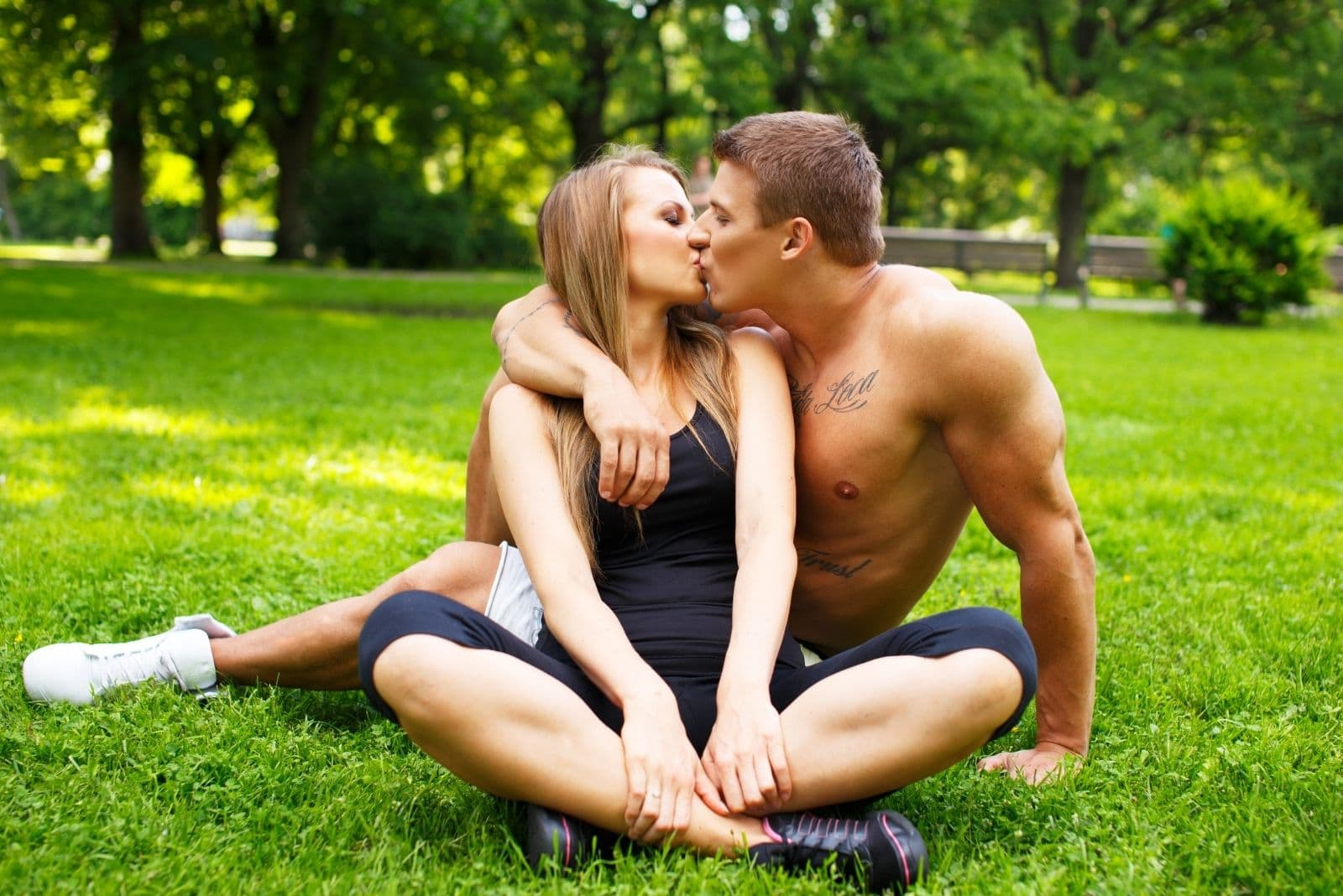 couple kissing while sitting on the green grass in the park