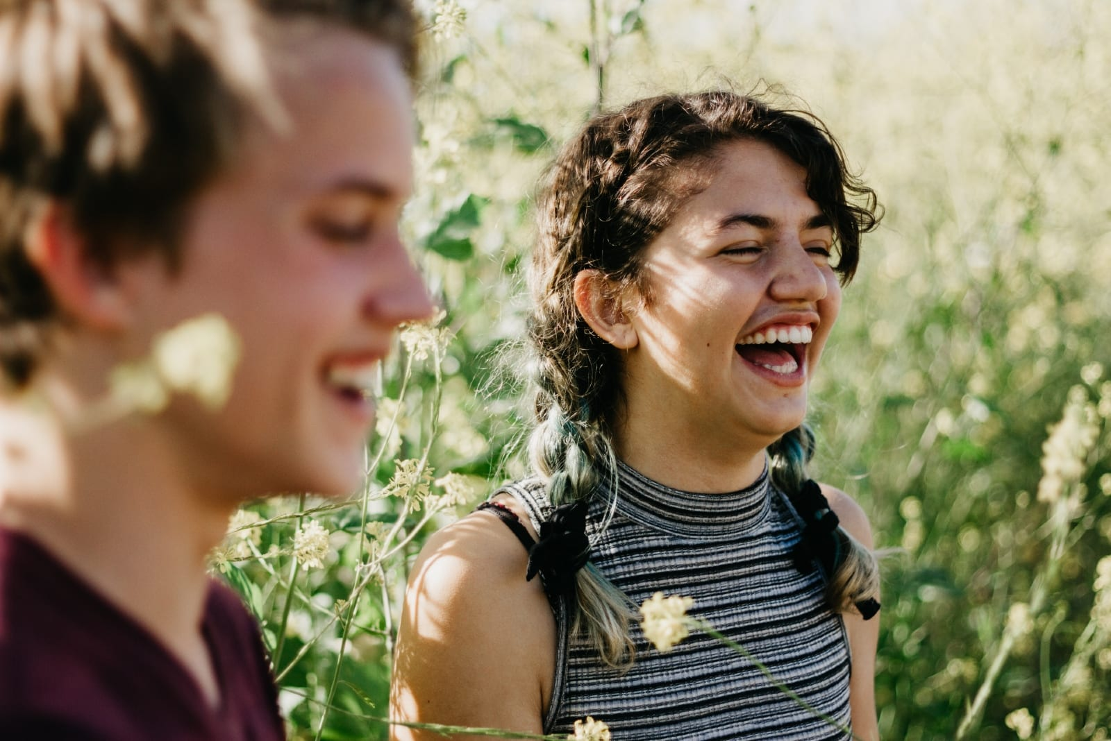 man and woman laughing surrounded with green grass
