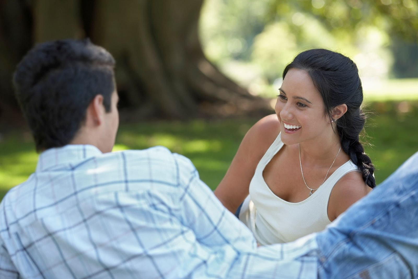couple lying for picnic in the park talking and laughing
