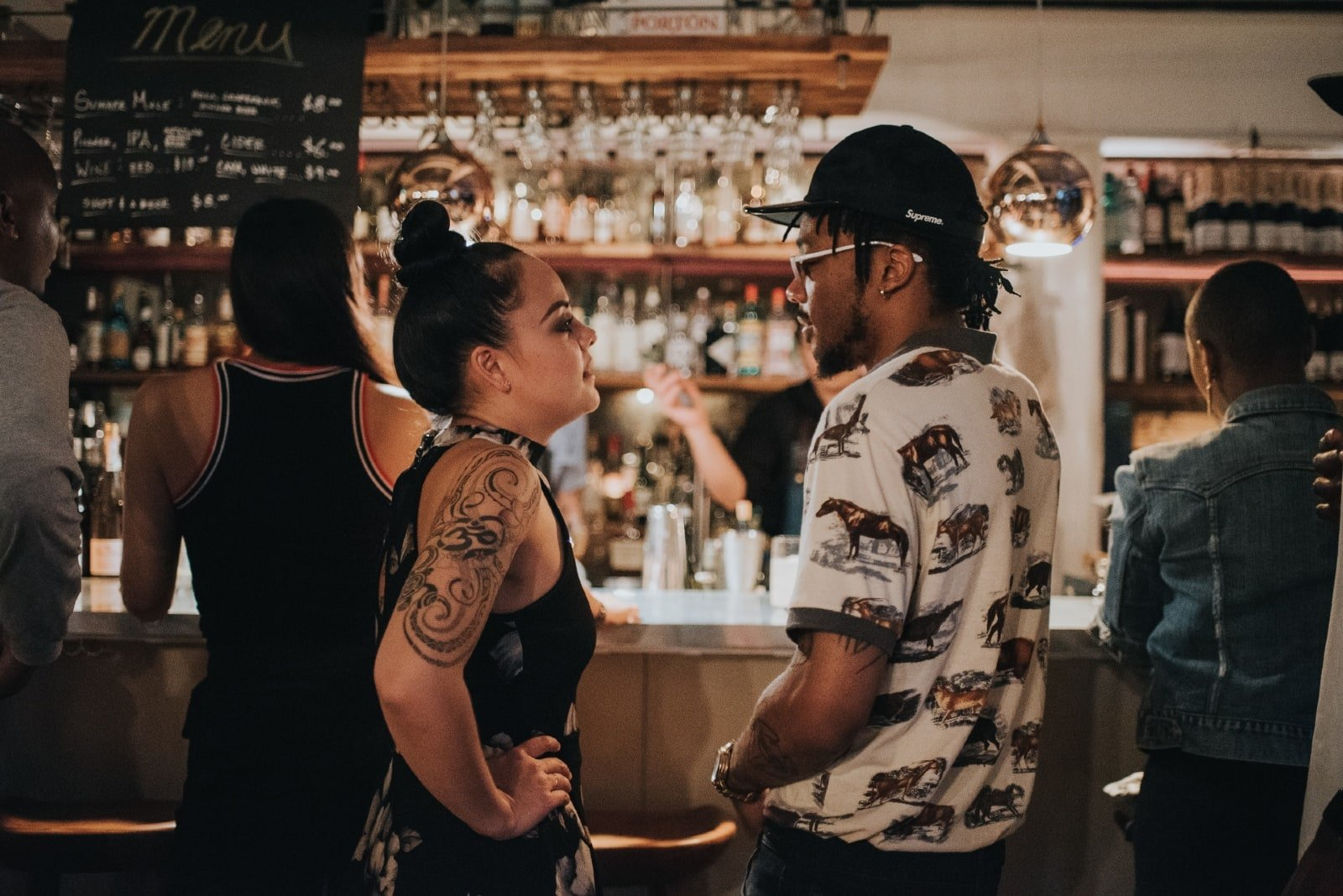 man and woman making eye contact while standing in bar