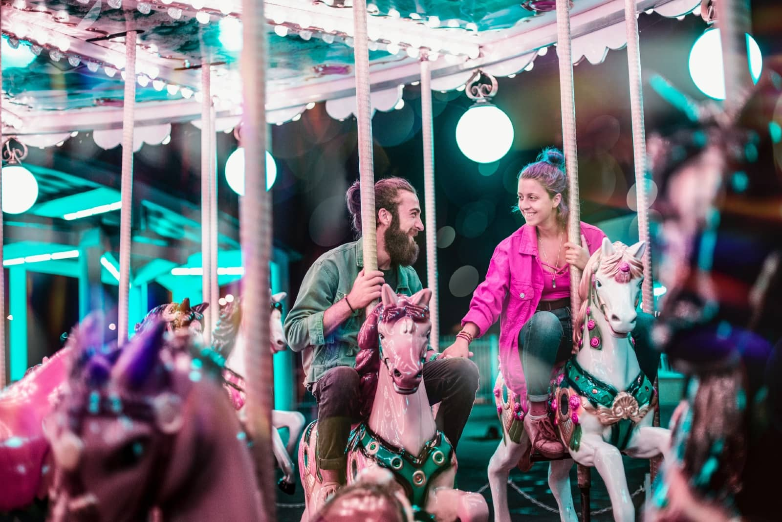 man and woman holding hands while riding a carousel