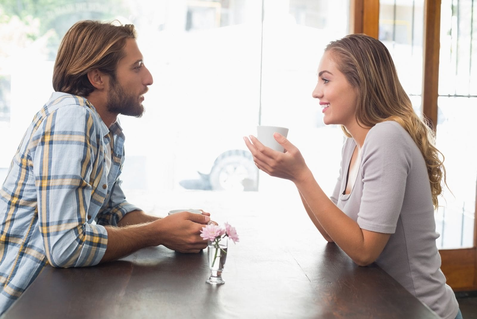 couple sitting face to face inside the cafe talking and smiling